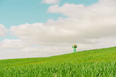 Back view of woman wearing green dress and summer hat standing on a field - ERRF03290