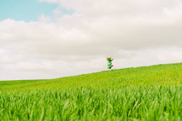 Back view of woman wearing green dress on a field jumping  in the air - ERRF03293