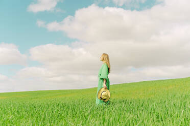 Blond young woman wearing green dress standing on a field - ERRF03296