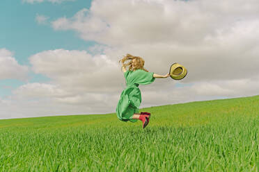Happy young woman wearing green dress jumping in the air on a field - ERRF03299
