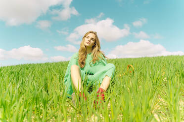 Portrait of blond young woman wearing green dress sitting on a field - ERRF03302