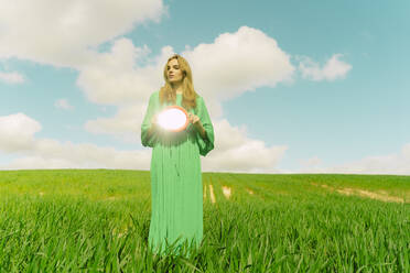 Young woman wearing green dress standing on a field holding reflecting mirror - ERRF03308