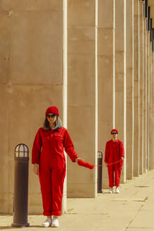 Young couple wearing red overalls and hats standing in a row connected with red string - ERRF03317