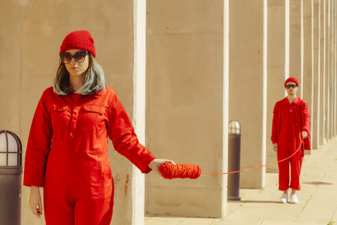 Young couple wearing red overalls and hats standing in a row connected with red string - ERRF03320