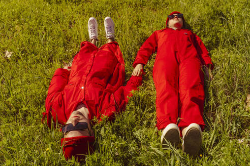 Young couple dressed in red lying on a meadow at sunlight - ERRF03323
