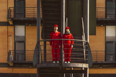Young couple wearing red overalls and hats standing side by side on platform - ERRF03344