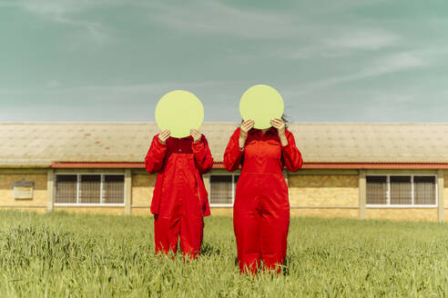 Young couple wearing red overalls  standing on a field hiding faces behind green circle - ERRF03353