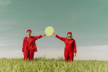 Young couple wearing red overalls  standing on a field holding green circle - ERRF03356
