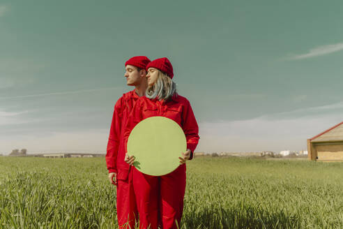Young couple wearing red overalls and hats standing on a field with green circle - ERRF03359