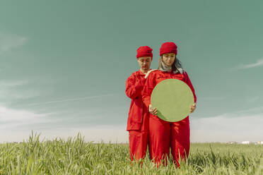 Young couple wearing red overalls and hats standing on a field with green circle - ERRF03362