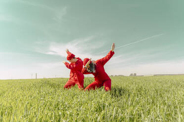 Young couple wearing red overalls and hats performing on a field - ERRF03365