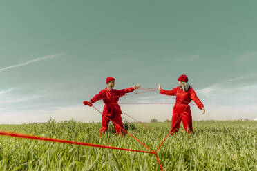 Young couple wearing red overalls and hats performing on a field with red string - ERRF03368