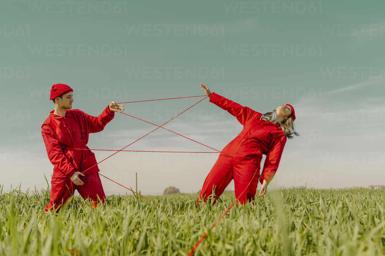 Young couple wearing red overalls and hats performing on a field with red string - ERRF03371 - Eloisa Ramos/Westend61