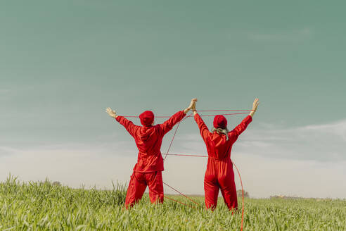 Back view of young couple wearing red overalls and hats performing on a field with red string - ERRF03374