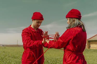 Young couple wearing red overalls and hats performing on a field with red string - ERRF03377