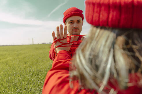 Portrait of young man dressed in red performing with his girlfriend on a field with red string - ERRF03380