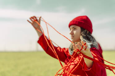 Young woman dressed in red performing with red string outdoors - ERRF03386