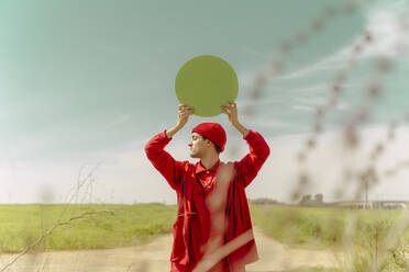 Young man dressed in red holding green circle - ERRF03389