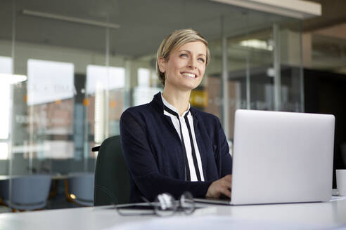 Smiling businesswoman using laptop in office - RBF07434