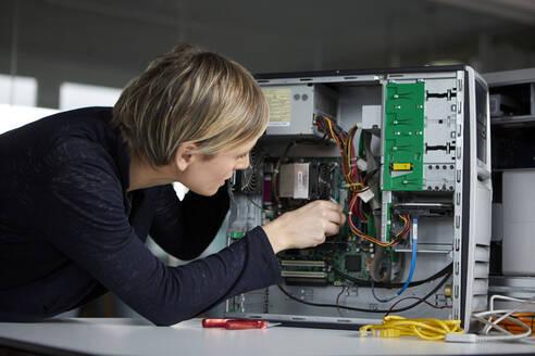 Woman assembling desktop pc in office - RBF07449