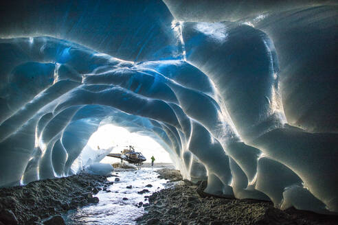 Helicopter parked next to entrance of ice cave during luxury tour. - CAVF78033
