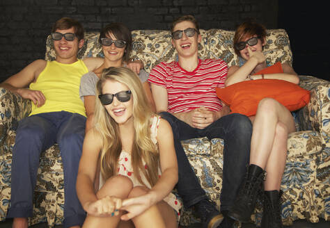 Portrait happy teenage friends in sunglasses on sofa at party - FSIF04648