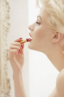 Profile glamorous young woman applying red lipstick - FSIF04684