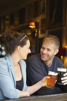 Happy couple drinking beer in pub - FSIF04690