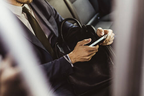 Midsection of businessman using smart phone while sitting in car - MASF17613