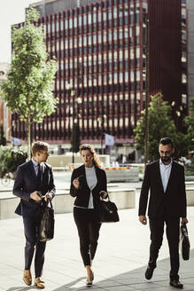 Entrepreneur discussing strategy with male and female colleagues while walking outdoors - MASF17628