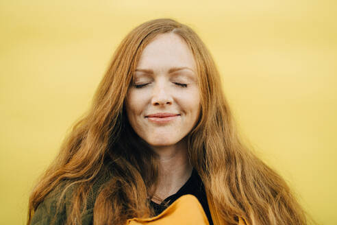 Smiling mid adult woman with eyes closed against yellow background - MASF17754