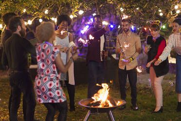 Friends with sparklers around fire pit at garden party - CAIF26013