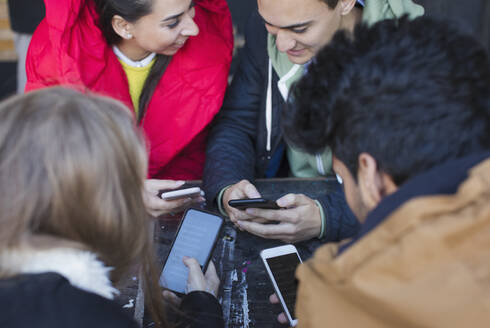 Young adult friends using smart phones at cafe table - CAIF26058