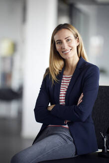 Portrait of smiling businesswoman in office - RBF07465