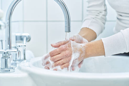 Woman washing her hand with soap - DIKF00409