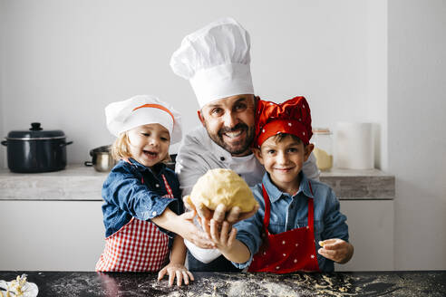 Portrait of father with two kids preparing dough in kitchen at home - JRFF04287