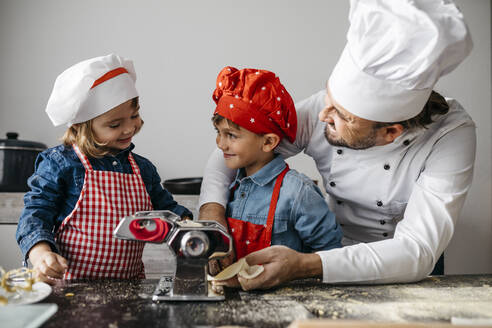 Father with two kids making homemade pasta with pasta machine in kitchen at home - JRFF04293