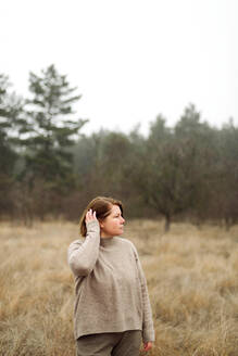 Woman standing by forest in foggy weather - CAVF78152