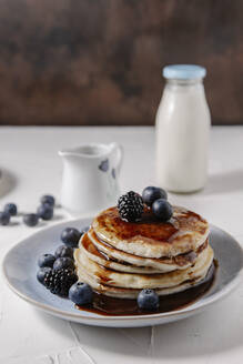 Pancakes topped with syrup and berries, with a bottle of milk in the background - CAVF78563