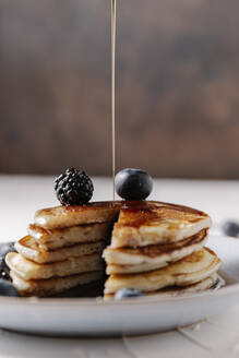Someone is pouring syrup on top of a stack of homemade pancakes - CAVF78569