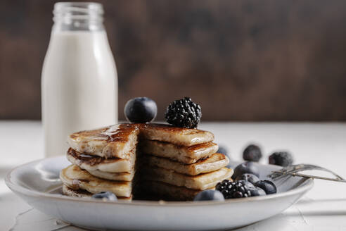 Still life of a stack of homemade pancakes with berries and syru - CAVF78575