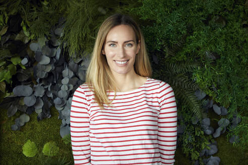 Portrait of smiling woman in front of a green wall - RBF07485