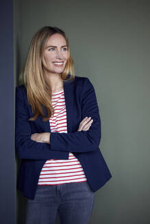 Portrait of smiling businesswoman leaning against a wall - RBF07488