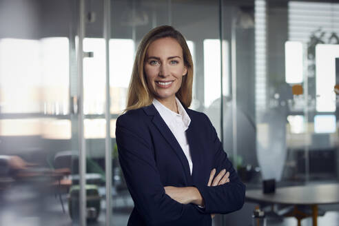 Portrait of smiling businesswoman in office - RBF07515