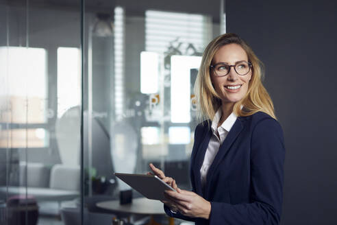 Smiling businesswoman using tablet in office - RBF07518