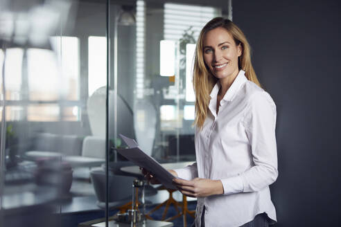 Portrait of confident businesswoman holding papers in office - RBF07521