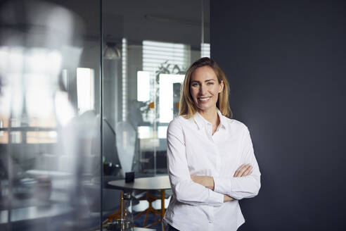Portrait of smiling businesswoman in office - RBF07527