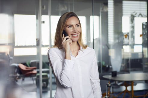 Portrait of smiling businesswoman on the phone in office - RBF07533