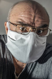 Portrait of senior man with surgical mask in panic - FRF00909