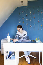 Girl sitting at desk at home doing homework - LVF08760